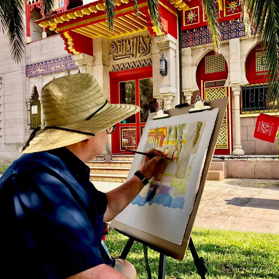 An artist painting the Villa Zorayda Museum outside
