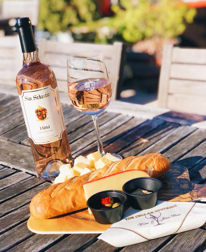Bottle and glass of The San Sebastian Rosa alongside a platter of cheeses and bread