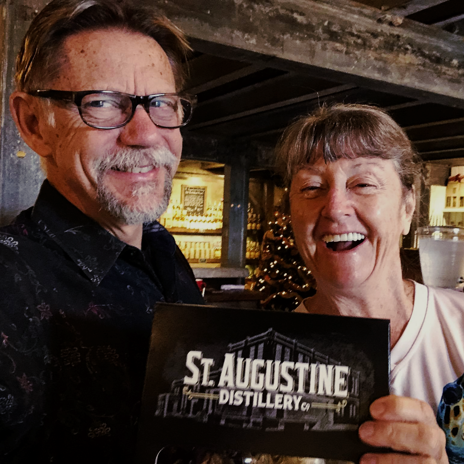 Patrons holding a sign of the St. Augustine Distillery